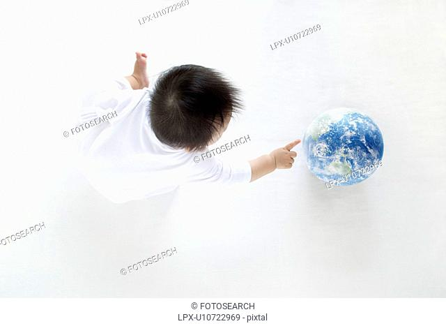 Baby Boy Playing With Globe, High Angle View
