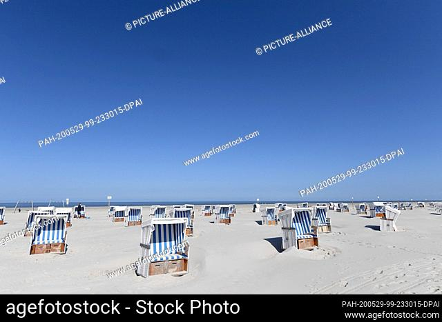 29 May 2020, Schleswig-Holstein, St.Peter-Ording: Beach chairs can be found on the North Sea beach under a blue sky. For the North Frisian islands and Halligen...