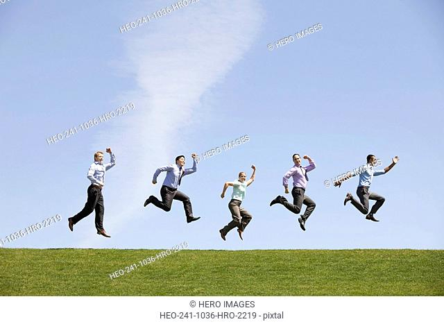 Group of confident business people jumping simultaneously