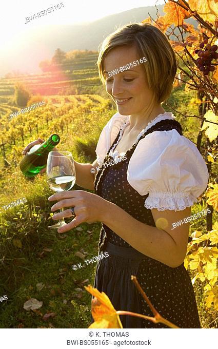 Wachau, young woman in traditional cloth, Blaudruckdirndl, with wine bottle and glass, Austria, Lower Austria, Wachau, Weissenkirchen
