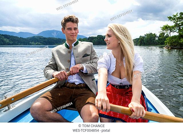 Germany, Bavaria, young couple wearing traditional clothes rowing together on Staffelsee