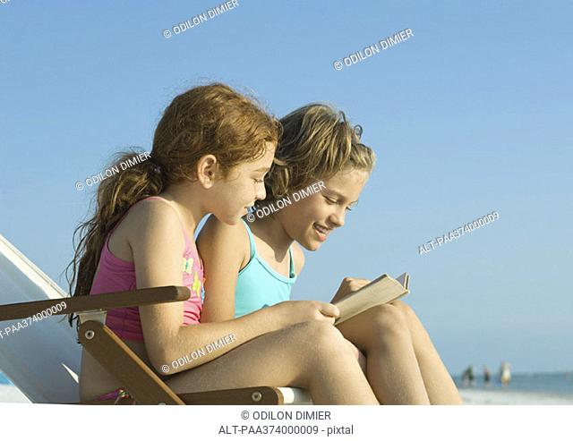 Two girls reading on beach