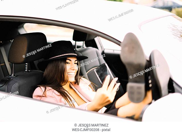 Businesswoman using smartphone and taking a selfie in the car