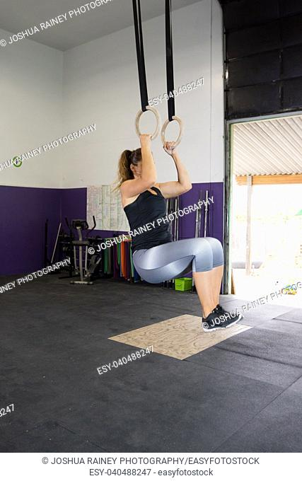 Muscular young woman doing fitness exercises on rings at a crossfit type gym