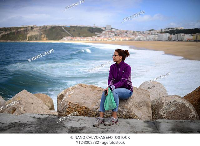 Young woman watches the sea from the dock of Nazare, Portugal