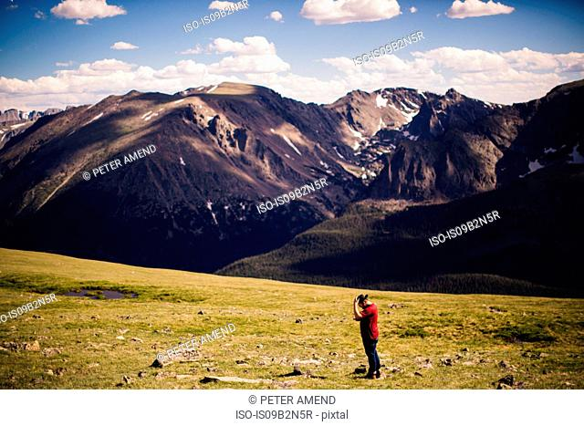 Man wearing cowboy hat by mountains, Rocky Mountain National Park, Colorado, USA