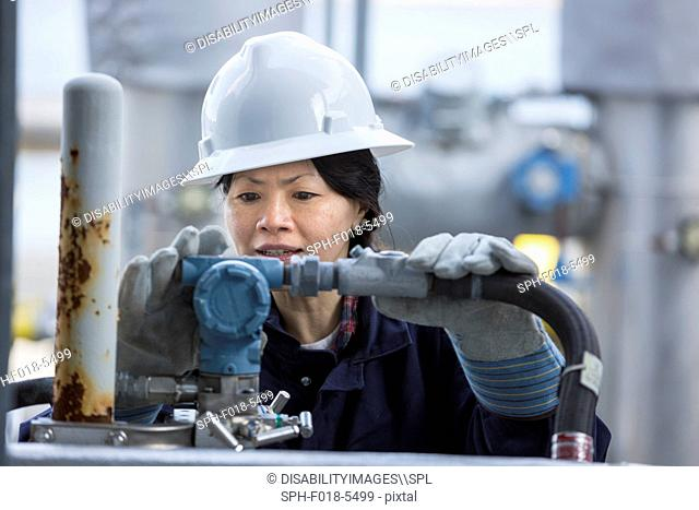 Female power engineer checking transducer at power station