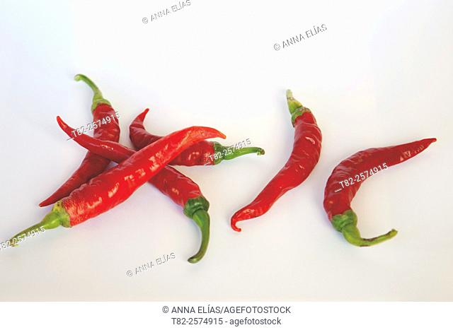 six red chilli peppers on white background