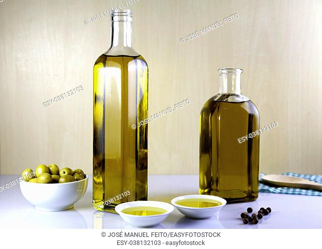 Two bottle olive oil with two test plate, olives, wood spoon, olives bowl and Peppercorns on brown and white