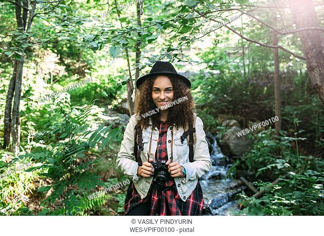 Portrait of smiling teenage girl with camera in nature
