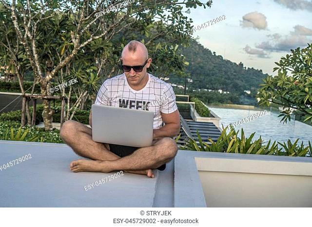 Outdoors portrait of handsome young man in sunglasses holding laptop computer on his knees while sitting on a rooftop over infinity swimming pool and sky...