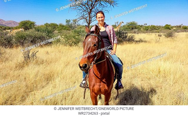 Namibia, Okapuka Ranch, Morning Ride with the Horse, Game Ride, Woman on Horse with Giraffe in the Background, Giraffe