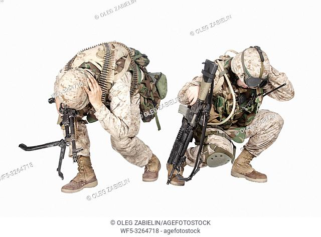 Two army soldiers in camo uniform, armed with assault rifle and machine gun, crouching to ground, holding helmets and covers ears with hands isolated on white...