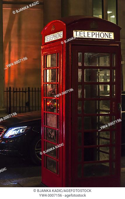 Red telephone box and posh car behind it at night, London, UK
