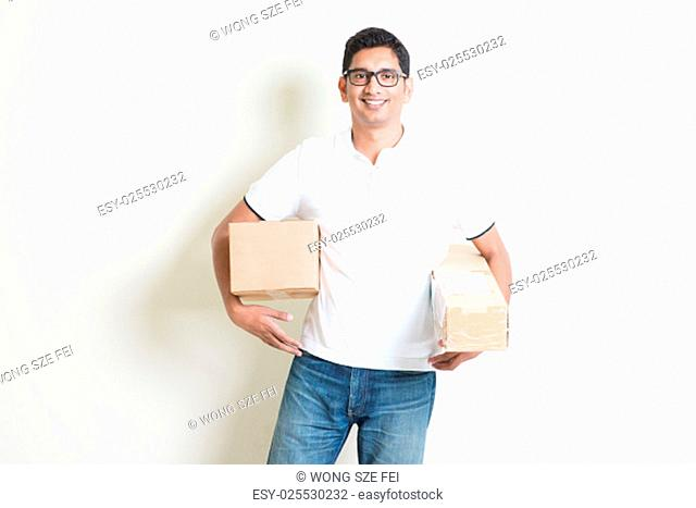 Courier delivery service concept. Happy Indian man received brown boxes, standing on plain background with shadow. Asian handsome guy model