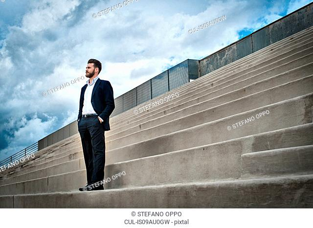 Low angle view of mid adult man on steps wearing suit, hands in pockets looking away