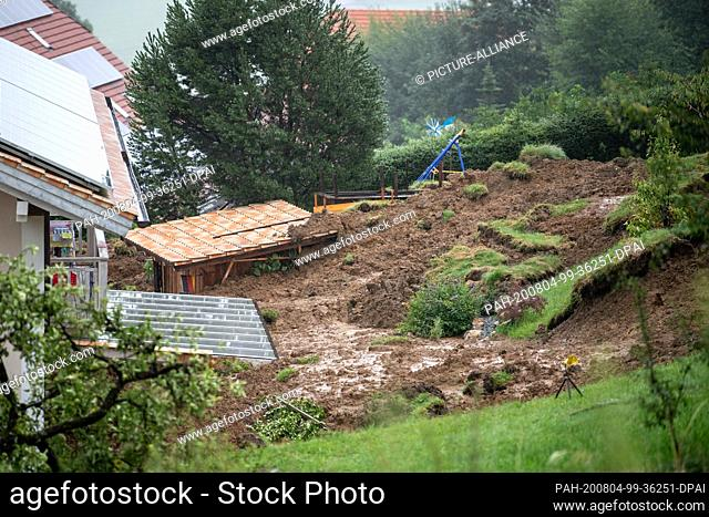 04 August 2020, Bavaria, Vachenlueg: The garden of a residential house is covered with earth and mud. Due to the continuous rain