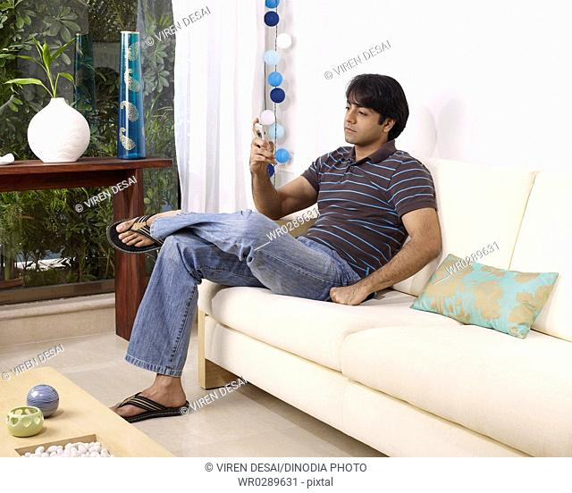 Young man operating mobile sitting on sofa MR702V