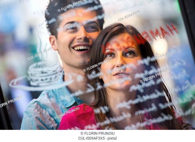 Young couple reading cafe window menu, Paris, France