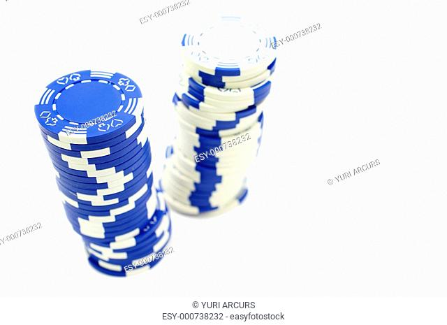 Two leaning stacks of poker chips - one blue and one white