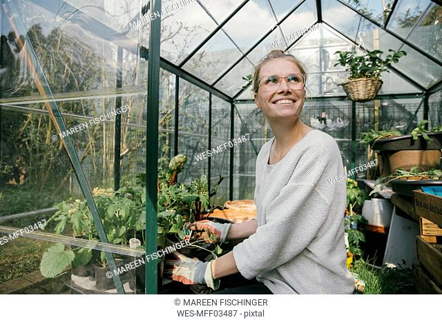 Portrait of happy young woman in her greenhouse