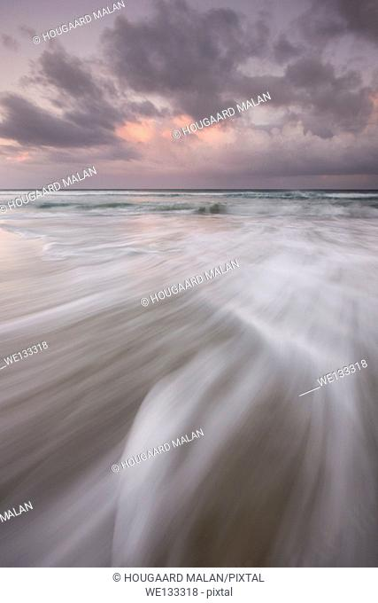 Landscape photo of waves washing across a beach below a colourful stormy sky. Bettys Bay, Western Cape, South Africa