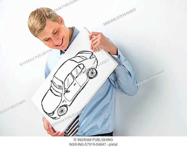 Young businessman holding sign with car sketch. Automobile dealer or credit agent