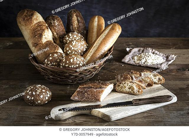 An assortment of bread in a basket and a baguette on the cutting board