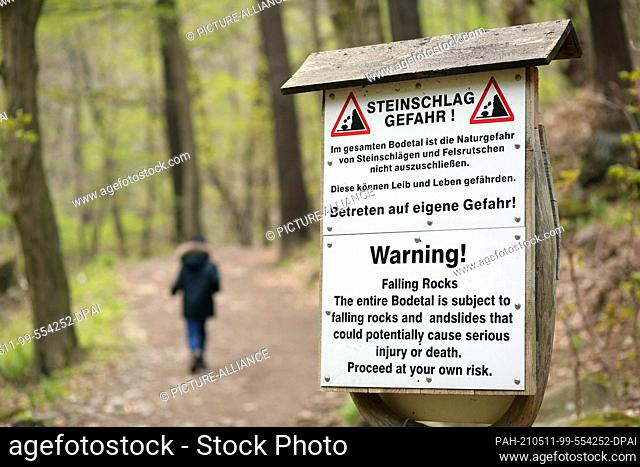 """07 May 2021, Saxony-Anhalt, Thale: A warning sign with the inscription """"""""Rockfall danger!"""""""" in the Bode Valley. The spring-like weather is again attracting many..."""