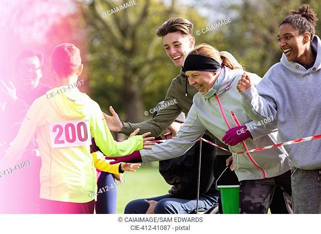 Spectators high-fiving runner at charity run in park