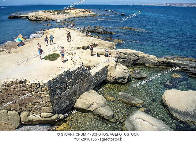 Tourists on the rocky coastline on the island of Tabarca Spain