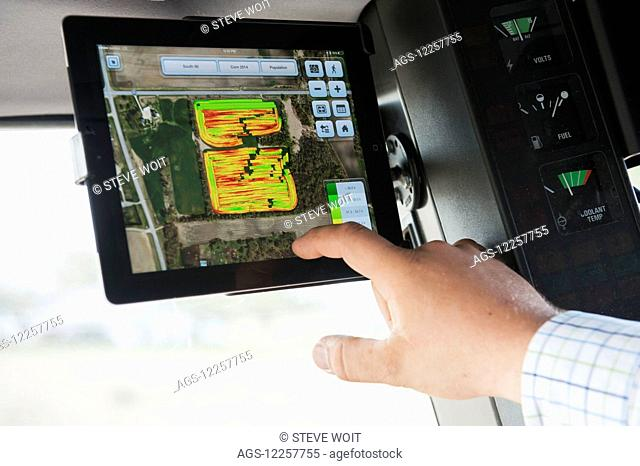 Farmer uses technology in tractor for soybean harvesting; Minnesota, United States of America