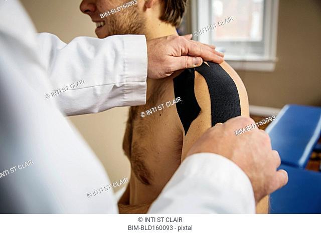 Caucasian doctor applying tape to shoulder of patient