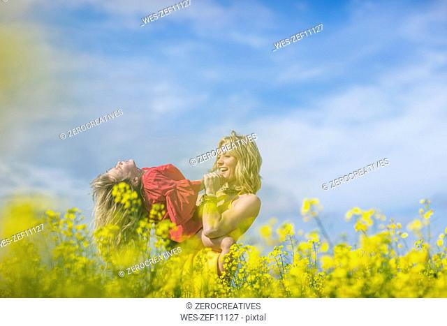 Mother and little daughter having fun together in rape field