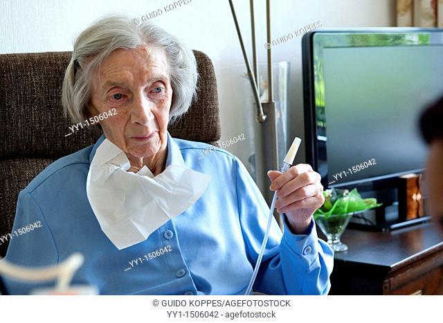 Rotterdam, Netherlands. A professional nurse of a Rotterdam nursing home helping an elderly inhabitant with her stomach pump