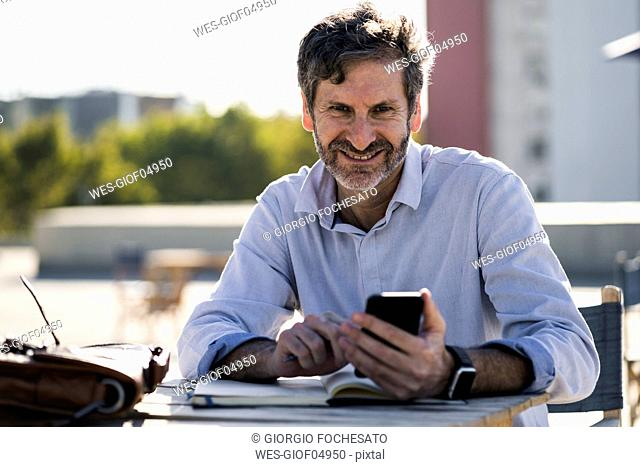 Portrait of smiling mature man sitting at outdoor table with cell phone and notebook