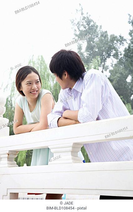 Chinese couple leaning on railing