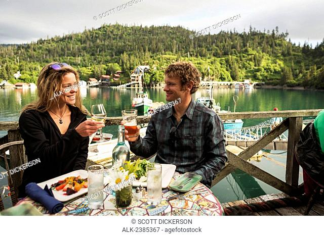 A couple in their 30's enjoys dinner at the Saltry Restaurant in Halibut Cove, Kachemak Bay, Southcentral Alaska