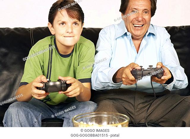 Middle-aged man and grandson playing video games
