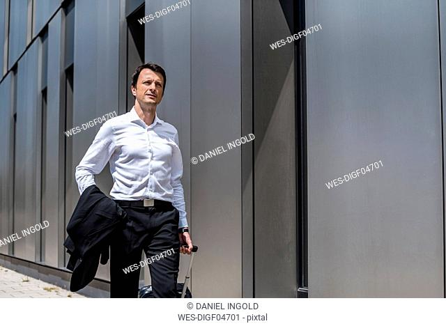 Businessman with rolling suitcase walking in the city