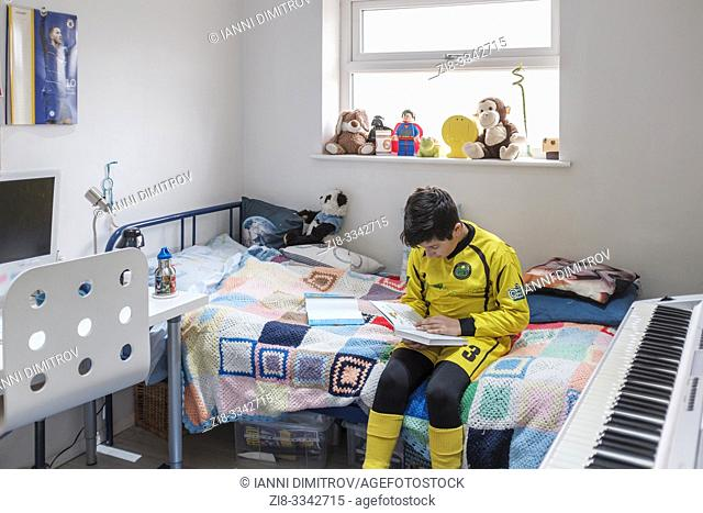 England, Uk-Young boy, 11 years in Little league football outfit reads a book in his bedroom
