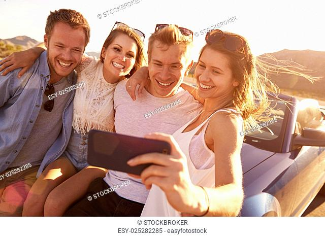 Friends On Road Trip Sit On Convertible Car Taking Selfie