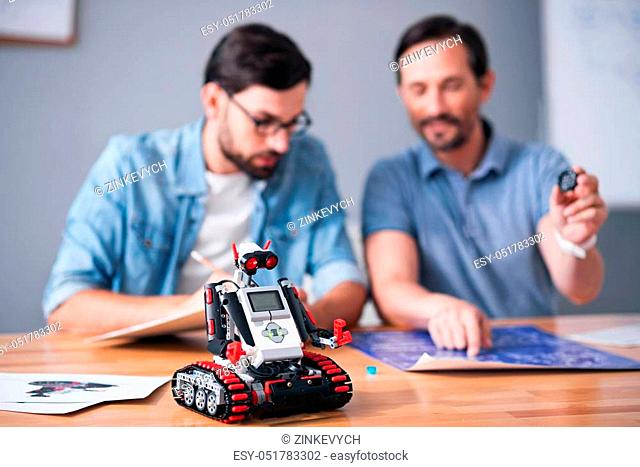 Upgrade technologies. Selective focus of robot standing on the table while professionals colleagues sitting in the background and working on the project