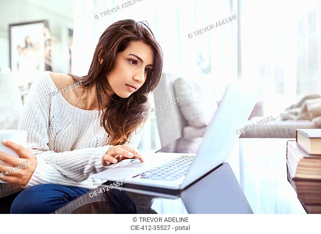 Serious woman using laptop at dining table