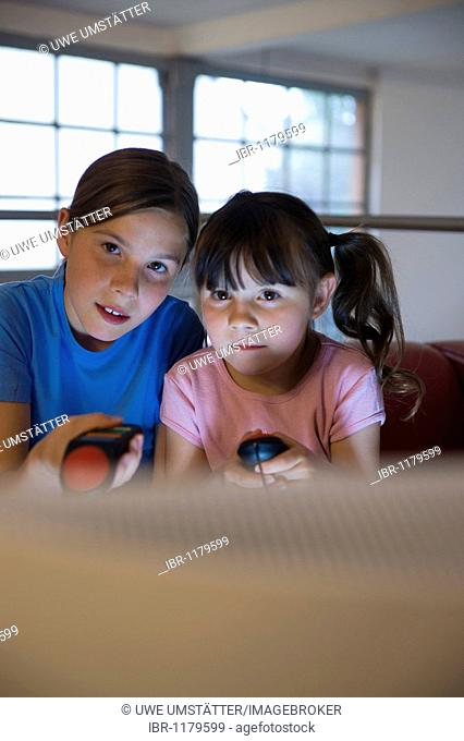 Two girls intently playing a video game