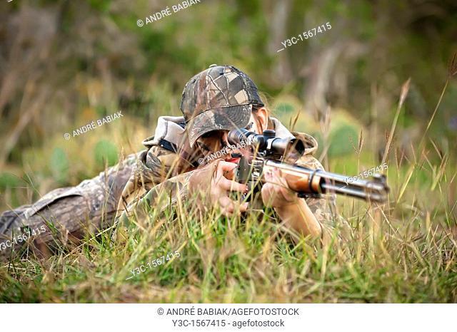 Hunting Season - female hunter lying on the ground ready to shoot rifle