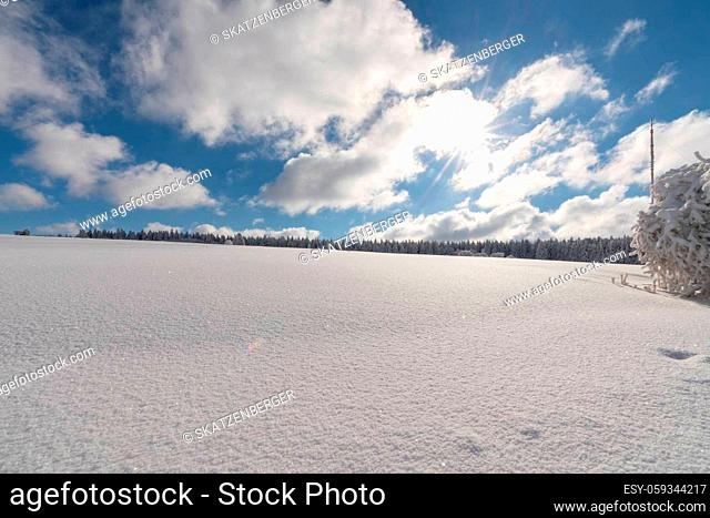 Beautiful winter wonderland in the mountains of Rhön with meadows and trees covered with snow and ice during a cold but sunny day in winter
