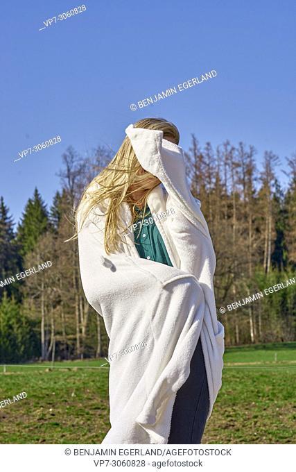 Portrait of woman in nature wearing a white bathrobe. Waakirchen, Bavaria, Germany