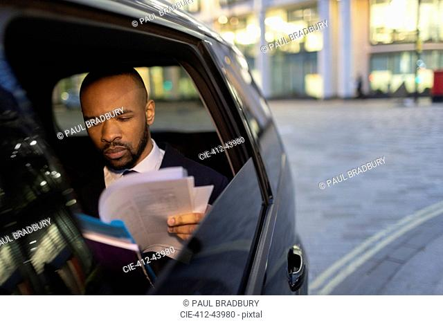 Businessman reading paperwork in crowdsourced taxi at night