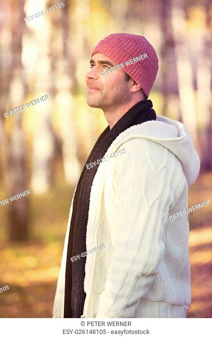 man standing between trees in fall and smiles